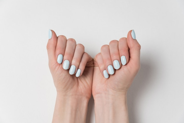Manucure féminine douce, vernis gel bleu. mains sur.