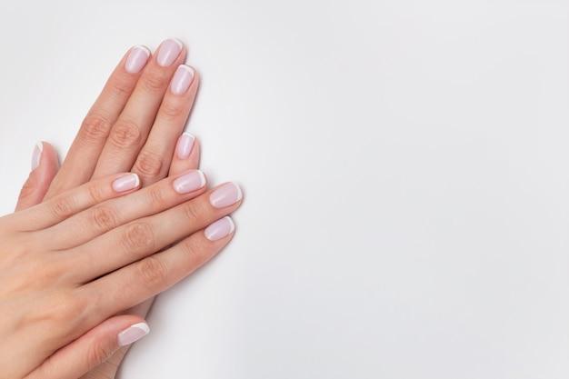 Manucure française. ongles nus recouverts de vernis gel sur fond blanc