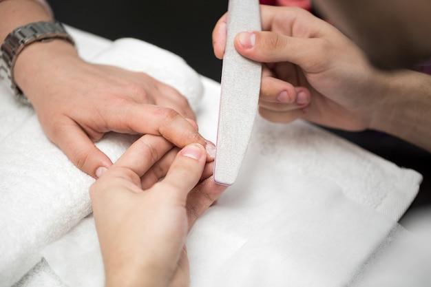 Manucure homme faisant de la manucure pour les femmes dans un salon de beauté