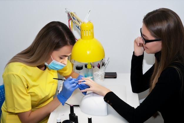 Manucure. manucure au salon. le maître manucure la fille, la beauté et la santé. processus de manucure. maître en masque et gants.