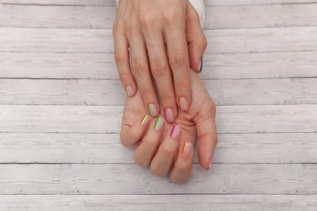 Manucure moderne multicolore, design des ongles. ambiance estivale, sur fond de bois. vue de dessus