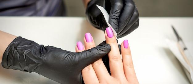 La manucure nettoie le vernis à ongles rose sur les ongles féminins