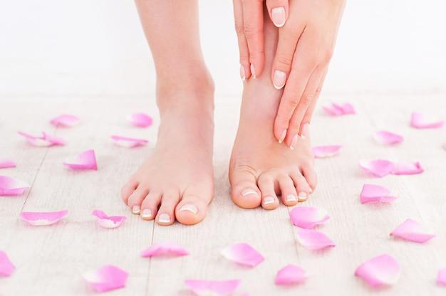 Manucure et pédicure. gros plan d'une jeune femme touchant ses pieds en se tenant debout sur un plancher de bois franc