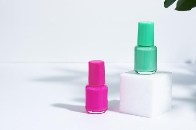 Manucure ou pédicure. maquette de bouteilles de cosmétiques isolées avec du vernis à ongles rose et vert