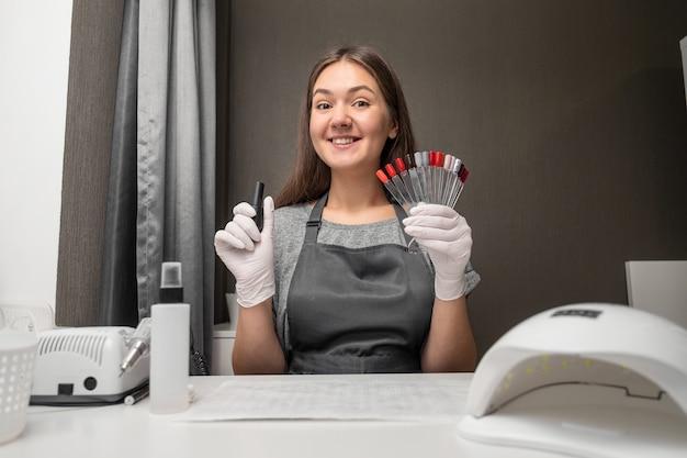 Manucure de profession heureuse jeune femme avec palette de couleurs de vernis et d'ongles