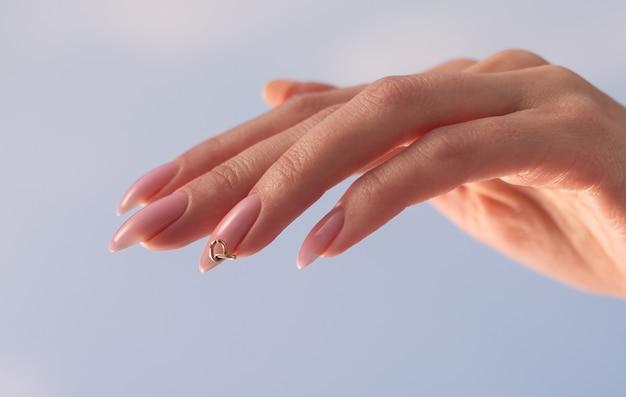 Manucure rose des mains de la jeune femme à la mode élégante des ongles