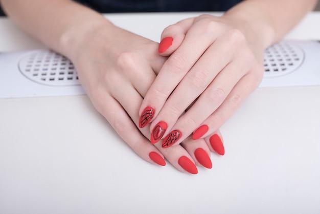 Manucure rouge avec un motif. mains féminines en salon de manucure