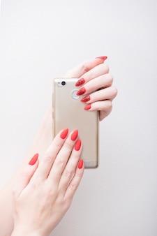 Manucure rouge avec un motif. téléphone intelligent dans une main féminine. fond blanc