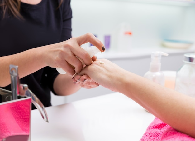 Manucure salon de beauté femme appliquant la crème pour les mains
