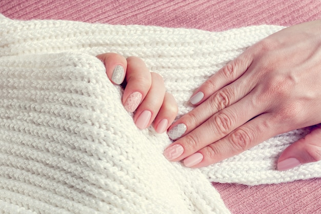 Manucure texture tricotée sur les ongles de couleurs roses et gris