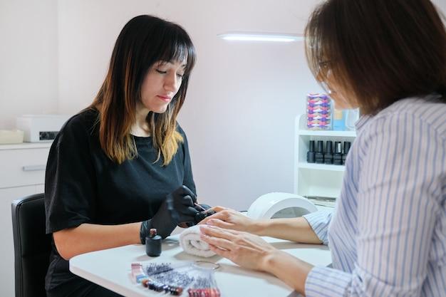 Manucure vernis ongles en gel. soins professionnels des mains et des ongles dans un salon de beauté