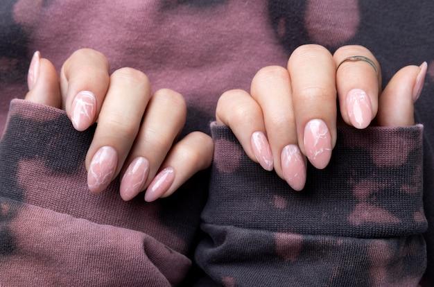 Manucured woman hands in trendy pink hoodie