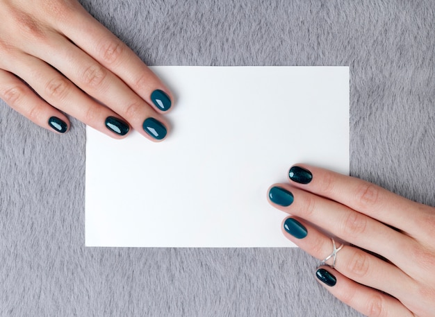 Manucured woman's hands holding postcard on grey furry table