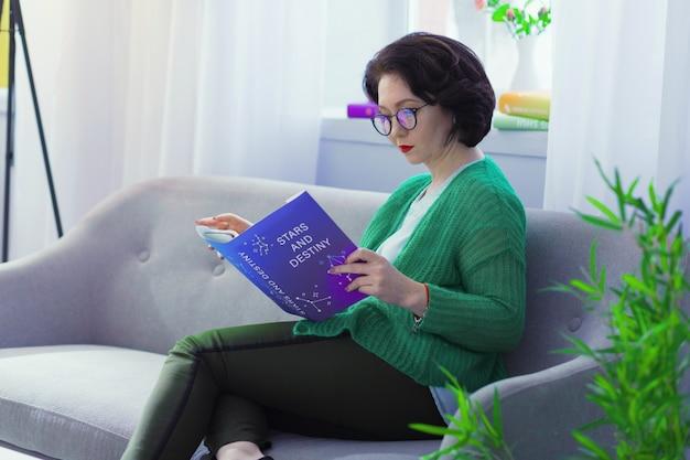 Manuel d'astrologie. femme brune intelligente assise avec un livre sur le canapé tout en étudiant l'astrologie