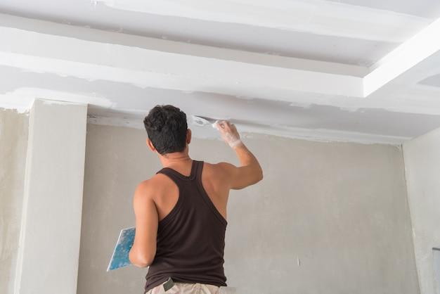 Manuel de travail avec outils de plâtrage mural à l'intérieur d'une maison.
