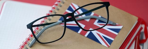 Le manuel et les verres de langue britannique sont sur la table