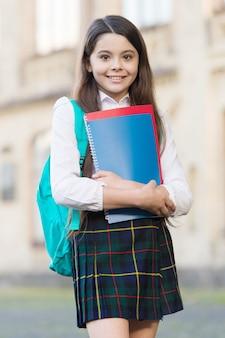 Manuels de littérature académique. un enfant heureux tient des livres de littérature. étudier la littérature à l'école. leçon de littérature. anglais et langue étrangère. bibliothèque de l'école. étude et éducation.
