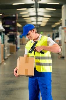 Manutentionnaire avec gilet de protection et scanner, scanne le code à barres du colis, il se tient devant l'entrepôt d'une entreprise de transport