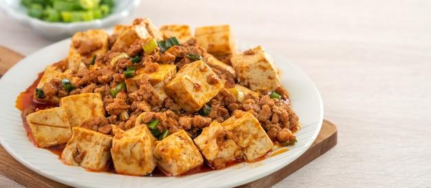 Mapo tofu, tofu sauté avec sauce piquante épicée en assiette blanche, cuisine gastronomique chinoise réputée.