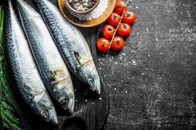 Maquereau cru sur une planche à découper avec de l'aneth, des épices et des tomates. sur table rustique sombre