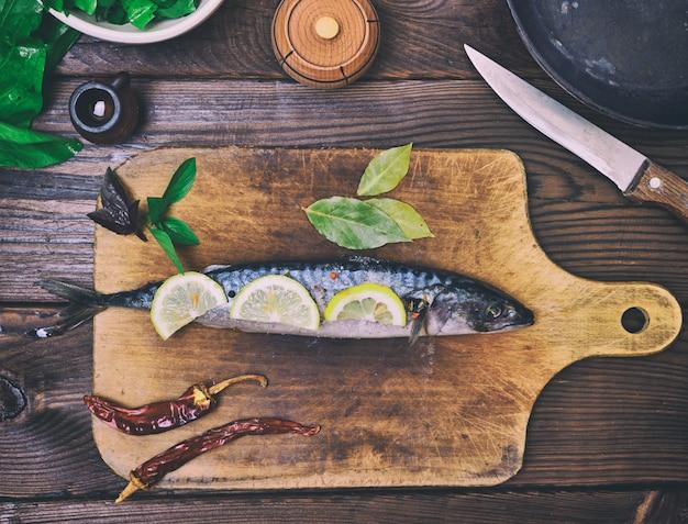 Maquereau frais sur planche de cuisine en bois