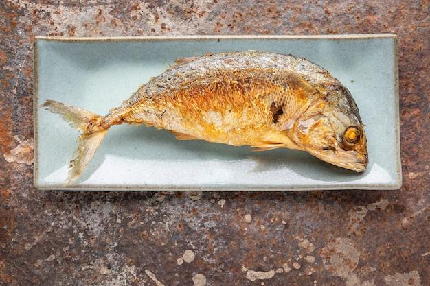 Maquereau frit dans une assiette en céramique rectangulaire sur fond de texture rouillée avec espace de copie pour le texte, vue de dessus