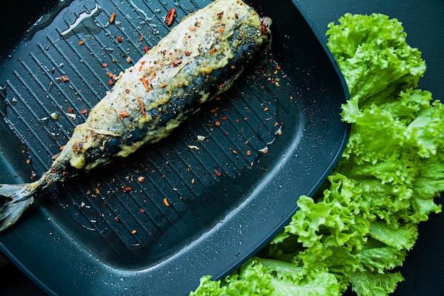 Maquereau frit dans une poêle à frire. nutrition adéquat. fond sombre.