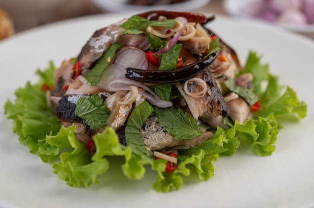 Maquereau frit garni de galanga, poivre, menthe, oignon rouge dans un plat blanc.