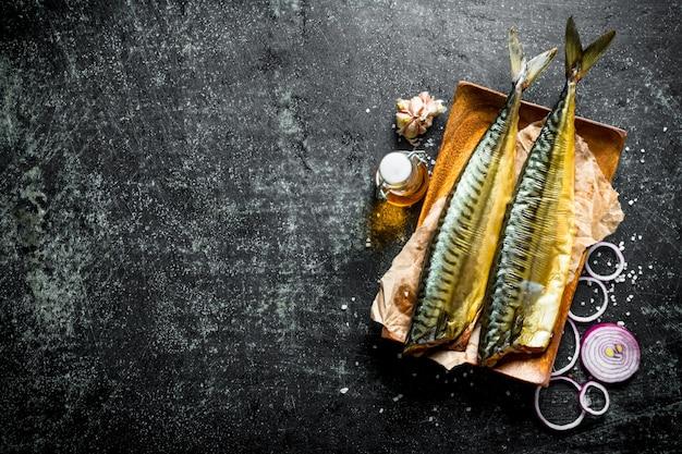 Maquereau de poisson fumé sur une assiette avec rondelles d'oignon et ail. sur fond rustique foncé