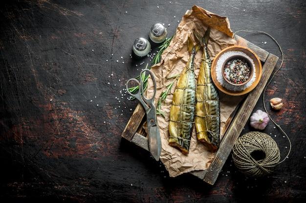 Maquereau de poisson fumé sur un plateau avec de la ficelle, des ciseaux et des épices. sur fond rustique foncé