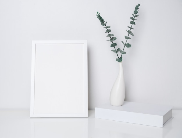 Maquette affiche blanche et livre avec des feuilles d'eucalyptus dans un vase en céramique moderne sur table blanche