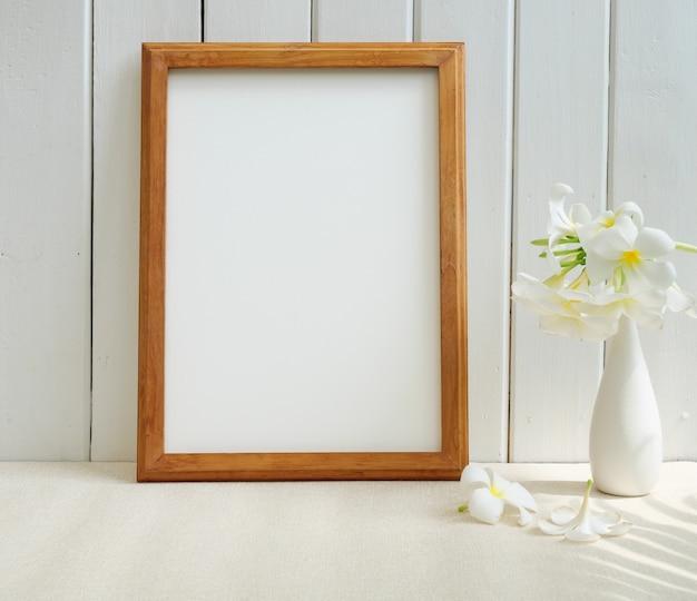 Maquette affiche cadre en bois et belle fleur tropicale de frangipanier dans un vase blanc moderne sur table beige et surface de mur en bois avec ombre de feuille de palmier