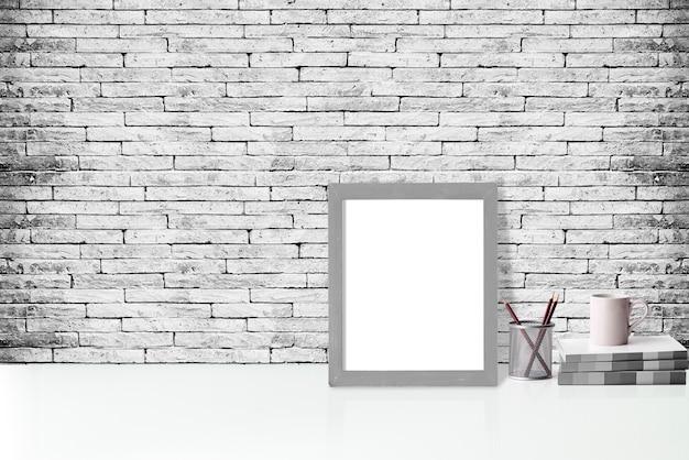 Maquette affiche ou cadre photo et fournitures sur table blanche, espace de bureau minimalisme hipster