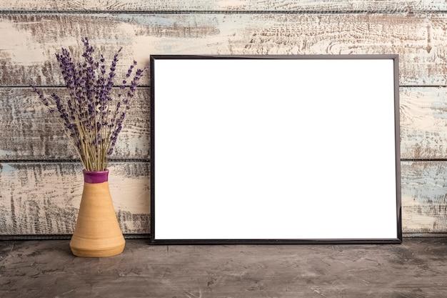 Maquette d'une affiche de cadre vide sur un mur de planches de bois. bouquet de lavande dans un vase