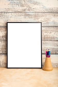 Maquette d'une affiche de cadre vide sur un mur de planches de bois. crayons de couleur dans un vase