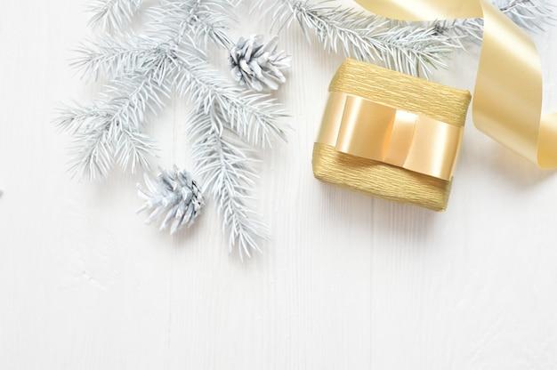 Maquette arbre de noël blanc, noeud beige, boîte-cadeau et cône. flatlay sur un blanc