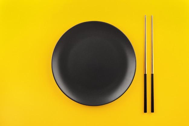 Maquette assiette ronde noire vide avec des baguettes dorées à plat sur fond jaune avec espace de copie.