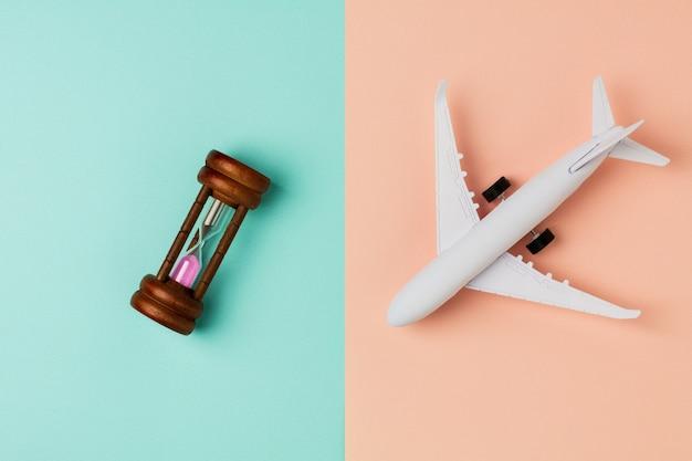 Maquette avion et sablier sur fond bleu et rose.