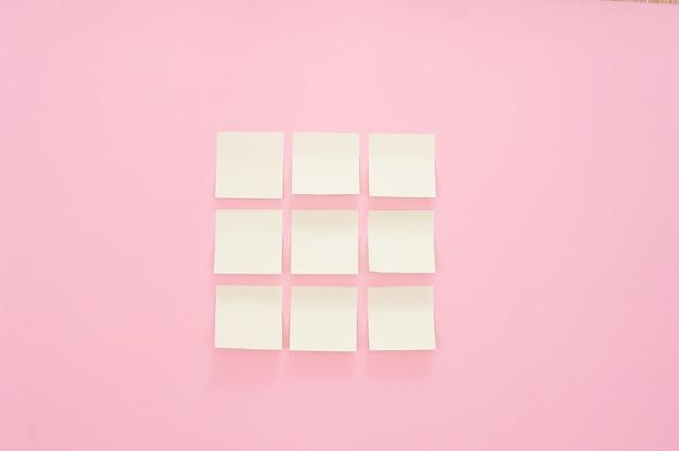 Maquette beaucoup d'autocollants de bureau vides de couleur sur fond rose