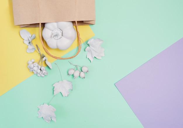 Maquette blanche avec citrouille, baies, feuilles et paquet sur un fond d'automne multicolore pastel