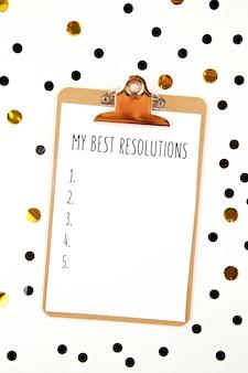 Maquette avec bloc-notes et confettis pour les résolutions du nouvel an