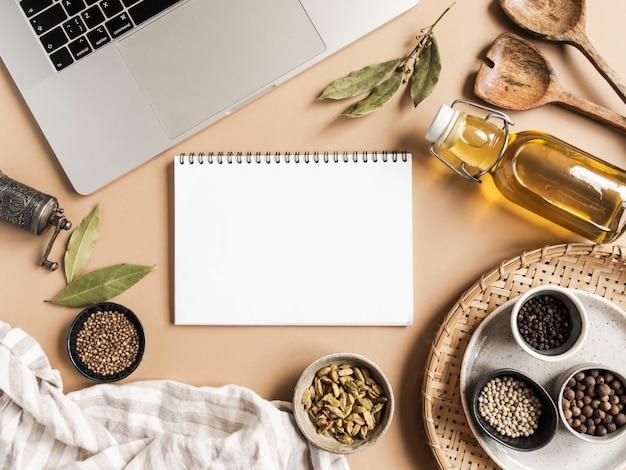 Maquette de bloc-notes de cuisine pour texte culinaire, ordinateur portable, huile en bouteille et épices