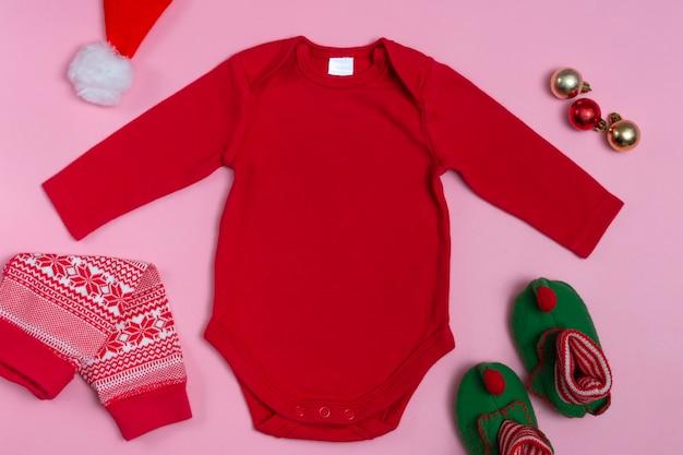 Maquette d'un body bébé du nouvel an à manches longues en rouge sur fond rose, décoré de chaussons gnome, pantalon rouge et décorations de noël, vue de dessus.
