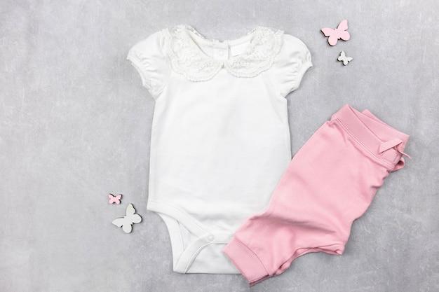Maquette de body bébé fille blanche à plat avec une culotte rose sur la surface de béton gris