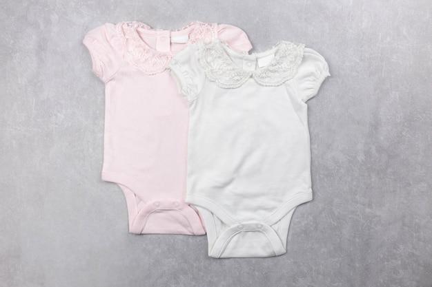 Maquette de body bébé fille blanche et rose à plat sur la surface de béton gris
