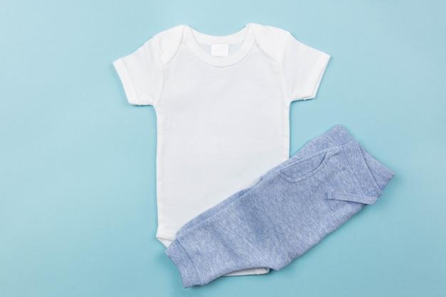 Maquette de body bébé garçon blanc à plat avec une culotte sur la surface bleue
