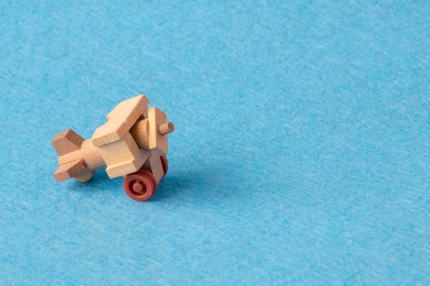 Une maquette en bois d'un vieil avion sur bleu