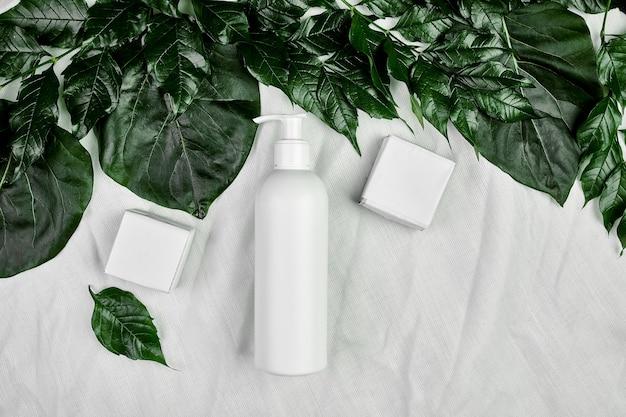 Maquette de bouteille blanche vierge sur des feuilles tropicales vertes, emballage cosmétique, vue de dessus de tube de crème, composition à plat
