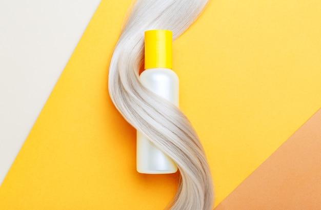 Maquette de bouteille de shampooing brin dans la boucle de verrouillage de cheveux blonds sur fond de couleur orange.