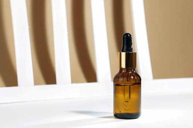 Maquette de bouteille en verre compte-gouttes sur fond gris géométrique jaune et blanc avec des ombres et des lignes de plantes dures. ombres dures. contexte cosmétique créatif.
